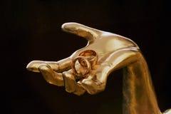 Två vigselringar i guld- hand Royaltyfria Bilder