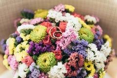 Två vigselringar ligger på en bukett av torkade blommor Fotografering för Bildbyråer