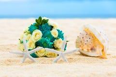Två vigselringar med sjöstjärna två och att gifta sig buketten och ett stort Arkivbilder