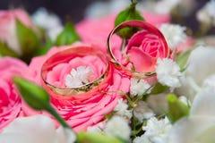 Två vigselringar och rosa och vita rosor Royaltyfria Bilder