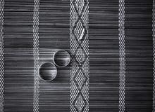 Två vigselringar på matt bambu Royaltyfri Foto