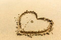 Två vigselringar som förläggas i en hjärta som dras i sanden arkivbilder