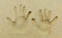 Två vigselringar som förläggas på fingrar i sanden fotografering för bildbyråer