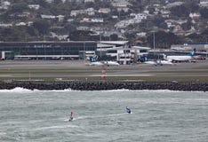 Två vindsurfare på den Lyall fjärden i Wellington New Zealand på en grå stormig dag Flygplatsen kan ses i bakgrunden arkivfoto