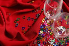 Två vinexponeringsglas med små kulöra hjärtor på ett rött gardintyg fotografering för bildbyråer