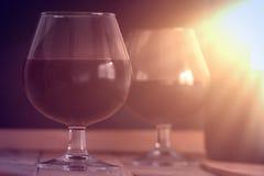 Två vinexponeringsglas och en flaska på en trätabell mot en svart bakgrund ljus sun Royaltyfri Fotografi