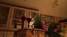 Två vinexponeringsglas på träjournaltabellen Härlig jul övervintrar dekoren för bröllopkopplingsceremoni med stearinljus, björk stock video