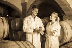 Två vinhusarbetare som kontrollerar kvalitet av produkten Royaltyfria Foton