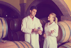 Två vinhusarbetare som kontrollerar kvalitet av produkten Arkivbilder