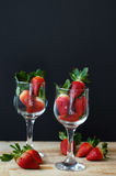 Två vinrankaexponeringsglas fyllde med den nya jordgubben på trätabellen Fotografering för Bildbyråer
