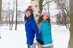 Två vinterkvinnor har roligt utomhus Arkivfoto