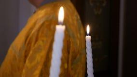 Två vita brinnande stearinljus i händerna av bruden och brudgummen på ollon i ortodox chirchbakgrund av en präst
