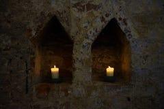 Två vita brinnande stearinljus itu nischer i en mörk gammal tegelstenvägg av en kloster, kopieringsutrymme royaltyfri bild