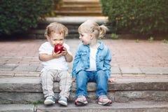 Två vita Caucasian gulliga förtjusande roliga barnsmå barn som sitter tillsammans att dela äta äpplemat arkivfoton