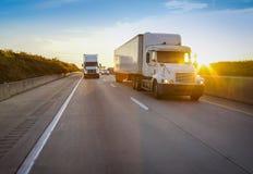 Två vita halva lastbilar på vägen Arkivbild