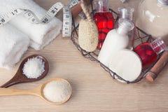 Två vita handdukar, korg med hampooen, kräm, lotionflaskor, wis arkivfoto