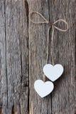 Två vita hjärtor som hänger på ett rep på en gammal riden ut träsu Royaltyfri Fotografi