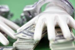 Två vita keramiska händer med handbojor på högen av 100 dollaranmärkningar Arkivfoton