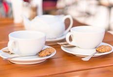 Två vita kopp te och skedar med kex Fotografering för Bildbyråer