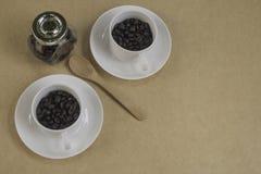 Två vita koppar med den kaffebönor, skeden och flaskan på brunt papper Fotografering för Bildbyråer