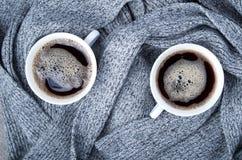 Två vita koppar med den varma kaffe och grå färghalsduken Royaltyfri Bild
