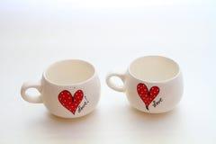 Två vita koppar med förälskelsemotiv Arkivbilder