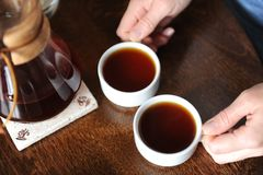 Två vita koppar med kaffe i händer på tabellen Arkivbild