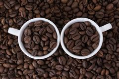 Två vita koppar med kaffebönor Royaltyfri Fotografi
