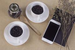 Två vita koppar med kaffebönor, anteckningsbok, sked, mobiltelefon Fotografering för Bildbyråer