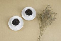 Två vita koppar med kaffebönor på brunt papper Royaltyfria Foton