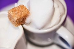 Två vita koppar med mjölkar mousse och kaffe med kubbruntsuger Royaltyfri Bild