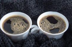 Två vita koppar med svart kaffe och skum är slutet Fotografering för Bildbyråer