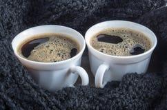 Två vita koppar med svart kaffe och skum Arkivbild