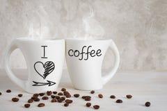 Två vita koppar med text älskar jag kaffe Arkivbild