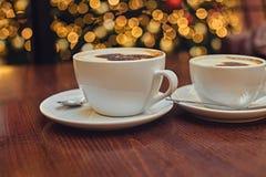 Två vita koppar med uppfriskande kaffe för arom Royaltyfri Bild