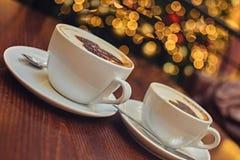 Två vita koppar med uppfriskande kaffe för arom Royaltyfria Bilder