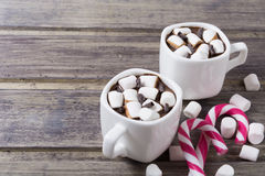 Två vita koppar med varm choklad och marshmallowen på den sjaskiga trätabellen Royaltyfria Bilder