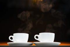 Två vita koppar med varma drinkar Arkivbild