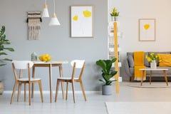 Två vita lampor ovanför en rund äta middag tabell i öppet utrymmeapartme royaltyfria foton