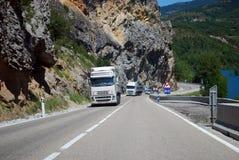 Två vita lastbilar till och med bergen Arkivfoto