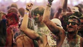 Två vita män som dansar, medan täckt i makt på en holifärgfestival stock video