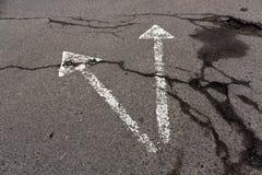 Två vita pilar på sprucken asfalttextur Royaltyfri Fotografi