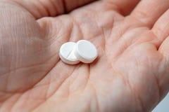 Två vita piller i hand closeup royaltyfri fotografi