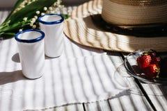 två vita porslinexponeringsglas, en hatt, liljekonvaljbukett, jordgubbar på en trätabell, solljus fotografering för bildbyråer