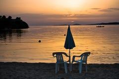 Två vita stolar på en strand på solnedgången i Sithonia Royaltyfri Foto