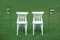 Två vita stolar som väntar på brudgummarna bredvid någon blom- garnering på det gröna gräset Arkivfoto
