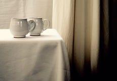Två vita tekoppar på en vit tabell mot en vit bakgrund royaltyfri foto