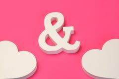 Två vitt trähjärta- och et-teckensymbol på rosa bakgrund arkivbilder