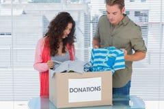 Två volontärer som ut tar kläder från en donationask Arkivfoto
