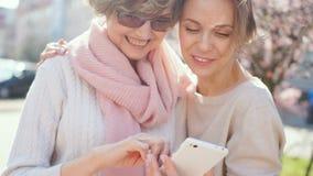 Två vuxna kvinnor med en smartphone i deras händer står på gatan mot bakgrunden av att blomma våren lager videofilmer